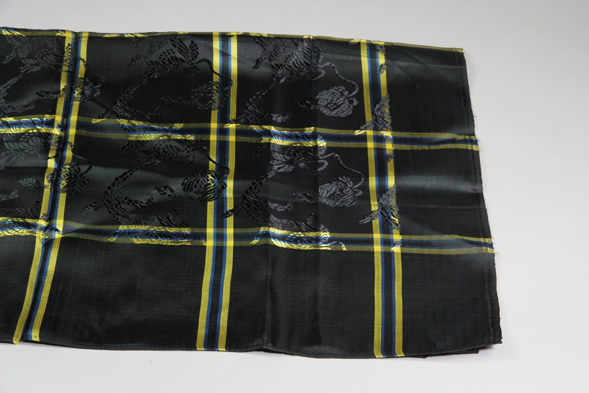 Kvadratisk svart sjal med gula och blå rutor i konstsiden. Den svarta botten har invävt blommönster. Smala handsydda fållar på två sidor, de andra två har stadkanter.