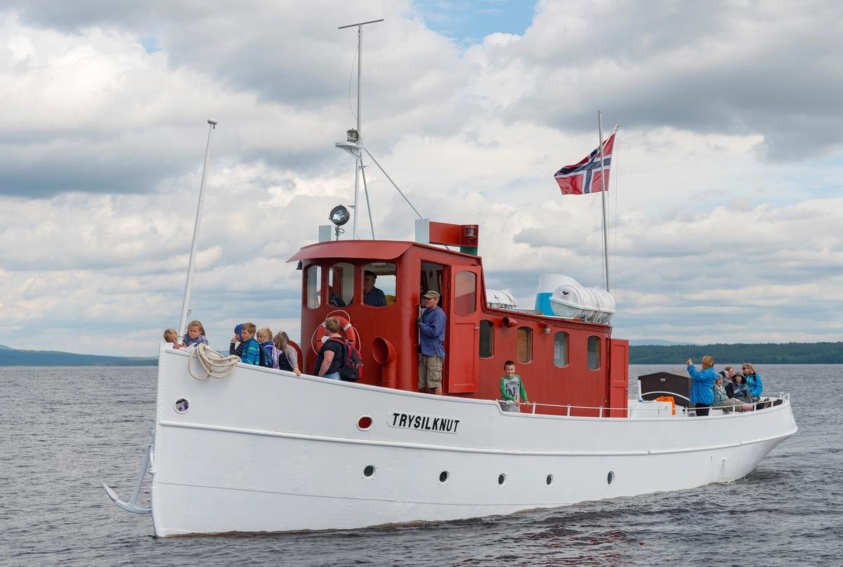 Slepebåten «Trysilknut» fotografert på den 47 kvadratkilometer store Osensjøen i grensetraktene mellom Åmot og Trysil i Hedmark, der Trysilknut gikk som tømmersleper fra 1914 til 1984.  Etter den tid har den 55 fot lange og 12 fot brede båten vært brukt som museumsbåt.  Den ble restaurert i perioden 2011-2014, og dette fotografiet er fra den første turen båten gjorde med passasjerer etter at restaureringa var avsluttet med maling av eksteriøret.  Skroget er kvitmalt og overbygningen (styrhus og bysse) er rødbrun.  Disse fargene har Trysilknut hatt siden båten ble ombygd fra damp- til dieseldrift i 1957-58, bortsett fra vulsten som markerer hvor rekka møter den nedre delen av skroget lenge var grønnmalt.  Da dette fotografiet ble tatt sto skipper Størk Olsen til rors, mens maskinist Allan Tutvedt sto i styrhusdøra.  De fleste av passasjerene var elever og ansatte fra Osen oppvekstsenter, som var spesielt invitert til denne båtturen, som inngikk i programmet ved 100-årsmarkeringa for båten 11. juni 2014.  Mer om Trysilknut og dens historie under fanen «Andre opplysninger».