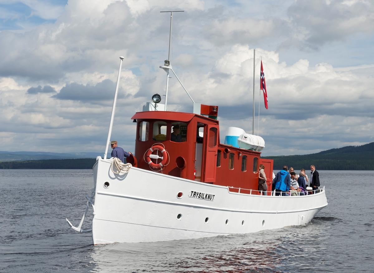 Slepebåten «Trysilknut» fotografert på den 47 kvadratkilometer store Osensjøen i grensetraktene mellom Åmot og Trysil i Hedmark, der Trysilknut gikk som tømmersleper fra 1914 til 1984.  Etter den tid har den 55 fot lange og 12 fot brede båten vært brukt som museumsbåt.  Den ble restaurert i perioden 2011-2014, og dette fotografiet er fra den første turen båten gjorde med passasjerer etter at restaureringa var avsluttet med maling av eksteriøret.  Skroget er kvitmalt og overbygningen (styrhus og bysse) er rødbrun.  Disse fargene har Trysilknut hatt siden båten ble ombygd fra damp- til dieseldrift i 1957-58, bortsett fra at vulsten som markerer hvor rekka møter den nedre delen av skroget lenge var grønnmalt.  Da dette fotografiet ble tatt sto skipper Størk Olsen til rors, og maskinist Allan Tutevdt befant seg på fordekket.  Passasjerene var gjester ved 100-årsmarkeringa for båten 11. juni 2014.  Blant dem skimter vi arkeologen Harald Jacobsen, direktør i Anno museum AS, lengst til høyre på akterdekket.  Mer om Trysilknut og dens historie under fanen «Andre opplysninger».