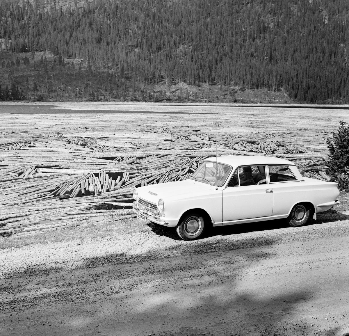 Tømmer på Engeren eller Engersjøen, fotografert under fløtinga i Trysilvassdraget i mai 1964. Fotografiet er tatt fra riksveg 26 – Engerdalsvegen.  I forgrunnen til høyre en personbil – en engelskprodusert Ford Cortina Mark I.    Mer informasjon om fløtinga i Trysilvassdraget i 1964 finnes under fanen «Opplysninger».