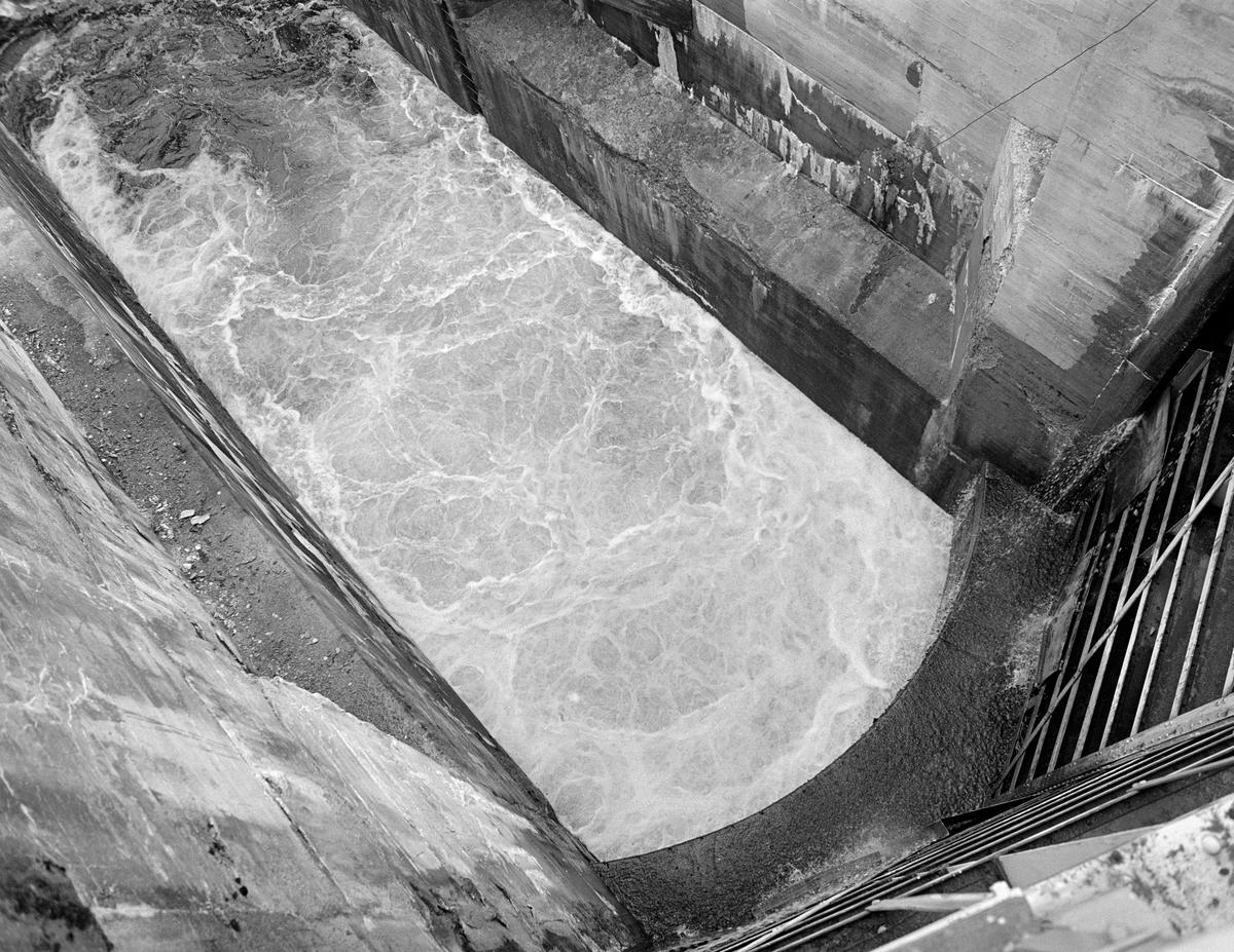 Fra et av slusekamrene ved Brekke sluser i tidligere Berg herred, nåværende Halden kommune, i Østfold.  Fotografiet er tatt fra en av sluseportene ned i et kammer som man nettopp hadde begynt å fylle med vann fra ovenforliggende slusekammer.  Slusekamrene ved Brekke hadde glatte, betongstøpte sidevegger og en kanal i golvet med overliggende spalterister.  Når slusekammeret skulle fylles med vann, ble det ført fra ovenforliggende kammer via omløpsrør som gikk forbi sluseporten og inn i kanalen i botnen av nedenforliggende kammer.  Løsningen med omløpsrøret, spalta og ristene skulle gi ei oppfylling av dette slusekammeret uten nevneverdig bølgedannelse, noe som kunne være et problem når tappinga skjedde via luker i sluseportene.  Også stålportene i Brekke-slusene hadde slike luker, men de ble bare brukt til finjustering av vannstanden.  På dette fotografiet ser vi «opprørt vann», uten store bølger komme opp fra kanalen i botnen av slusekammeret.  Fra sluseporten (nederst til høyre på bildet) drypper det bare litt fra noen lekkasjepunkter.  En liten historikk om tømmerfløting og kanaliseringsarbeid i Haldenvassdraget finnes under fanen «Opplysninger».
