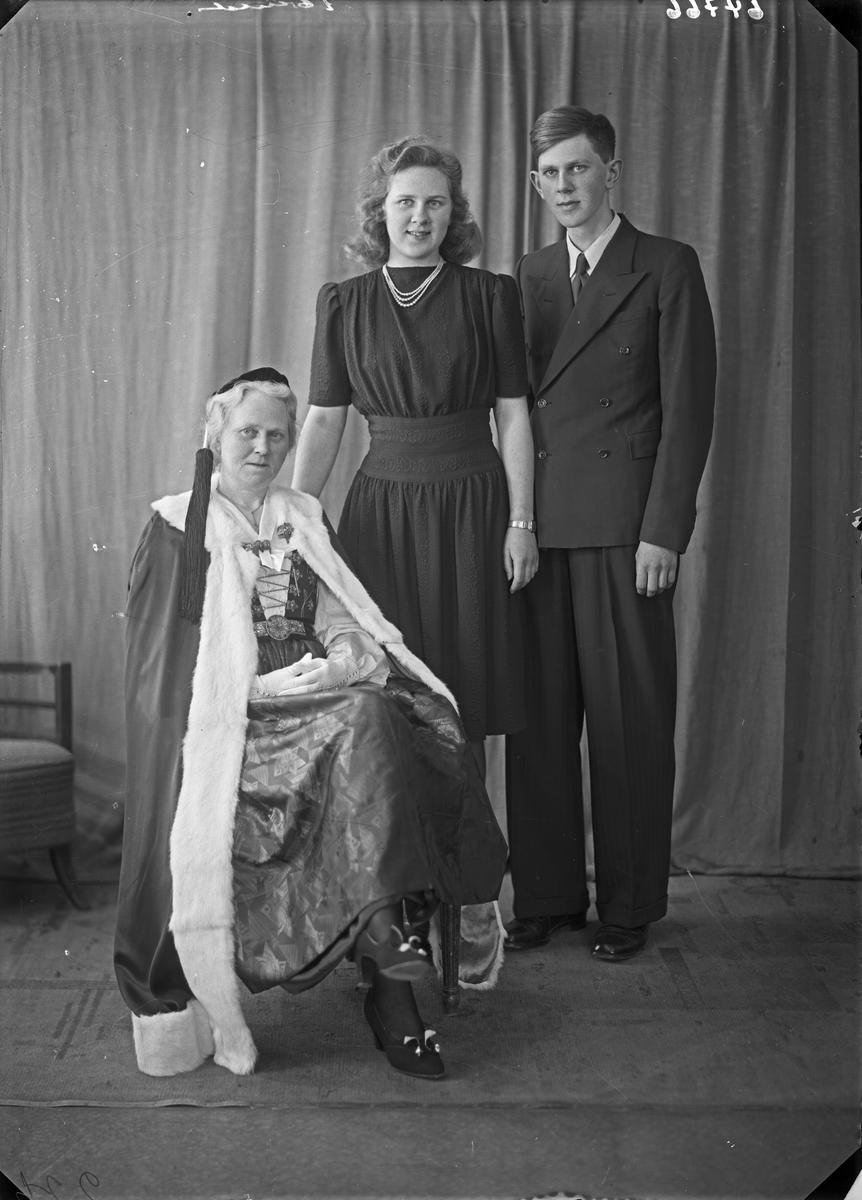 Portrett. Familiegruppe på tre. Eldre kvinne i folkedrakt, ung kvinne og ung mann. Mor, datter og sønn. Bestilt av Fru Knutsen. Skjoldaveien.