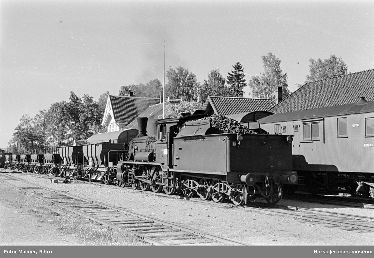 Grustog trukket av damplokomotiv type 18c nr. 134 i spor 2 (nærmest) på Roverud stasjon. I spor 1 står kryssende godstog.