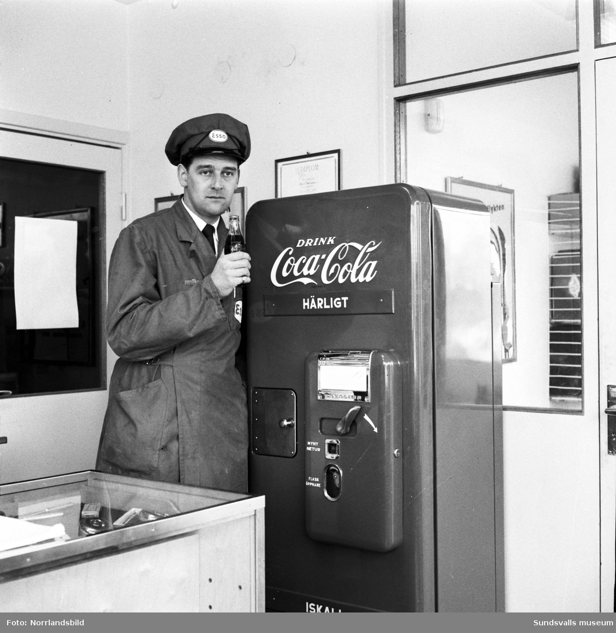 Föreståndaren på en Esso bensinstation demonstrerar en Coca-Cola-automat.