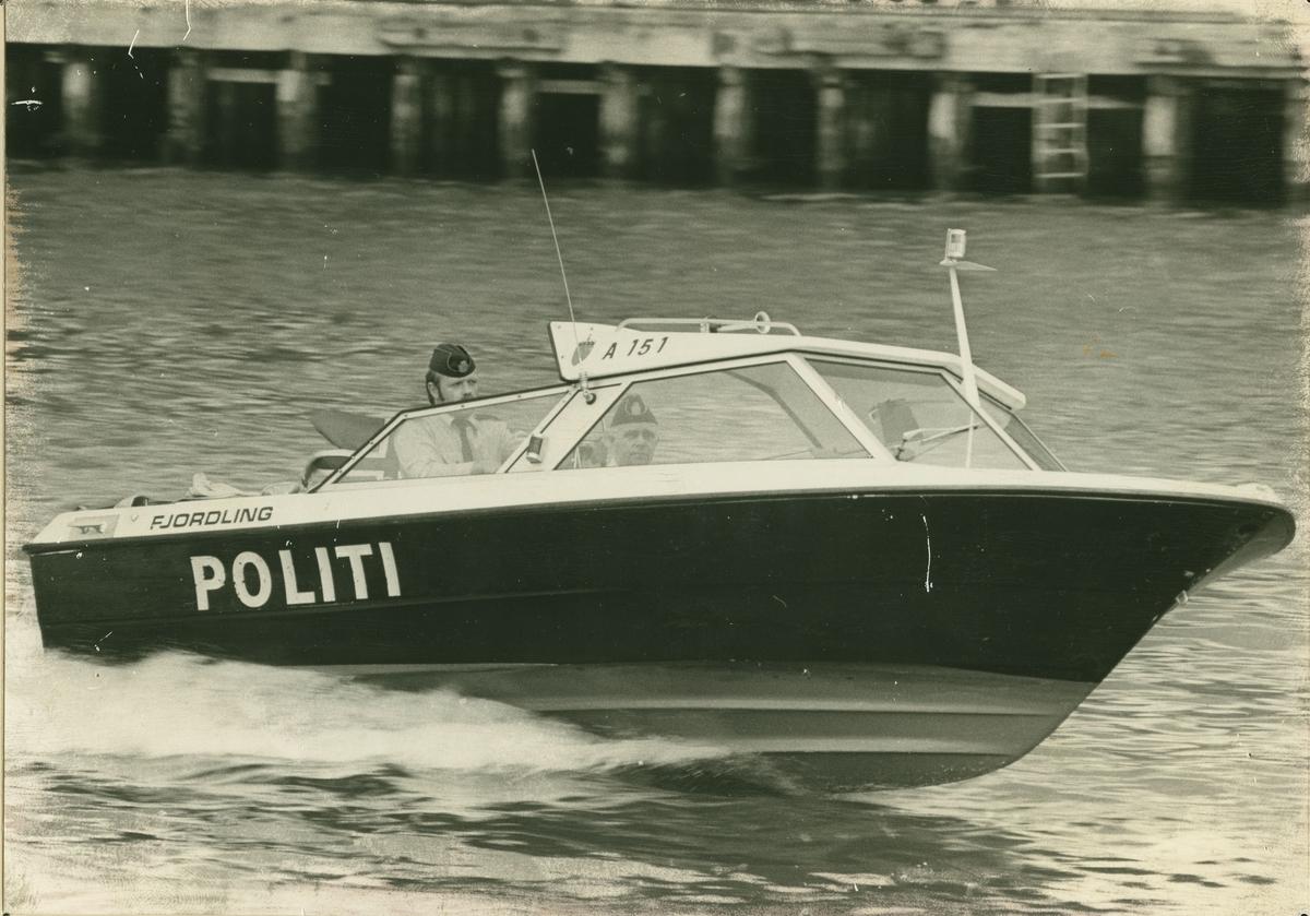 """Politibåt på vann med to politibetjenter ombord. Båten har """"Fjordling"""" på siden og nr A 151."""
