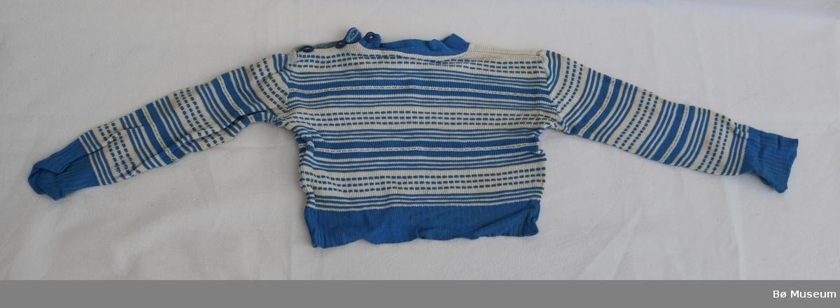 Barnegenser med stripete mønster og tre knappar i den høgre skuldra. Ribbestrikk nederst mot åpning og nederst på begge armane.