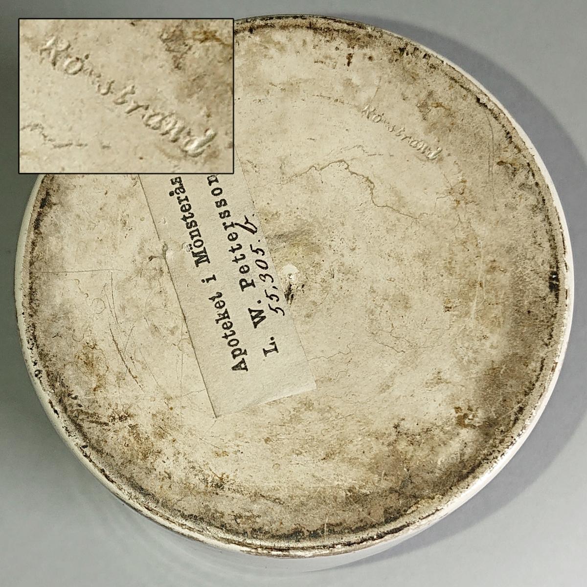Ståndkärl, burk, av vitglaserat flintgods. Cylindrisk med rak mynning. Platt lock av bleckplåt.