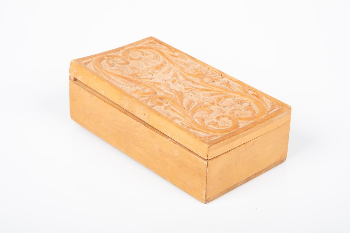 Skrin med lokk. Den er laget av tre og er lakkert. Lokket har utskåret dekor av akantus. Skrinet har tre oppbevaringsrom. Det er spor etter V-formede ben på undersiden av skrinet. Den ene kanten på lokket er løs.