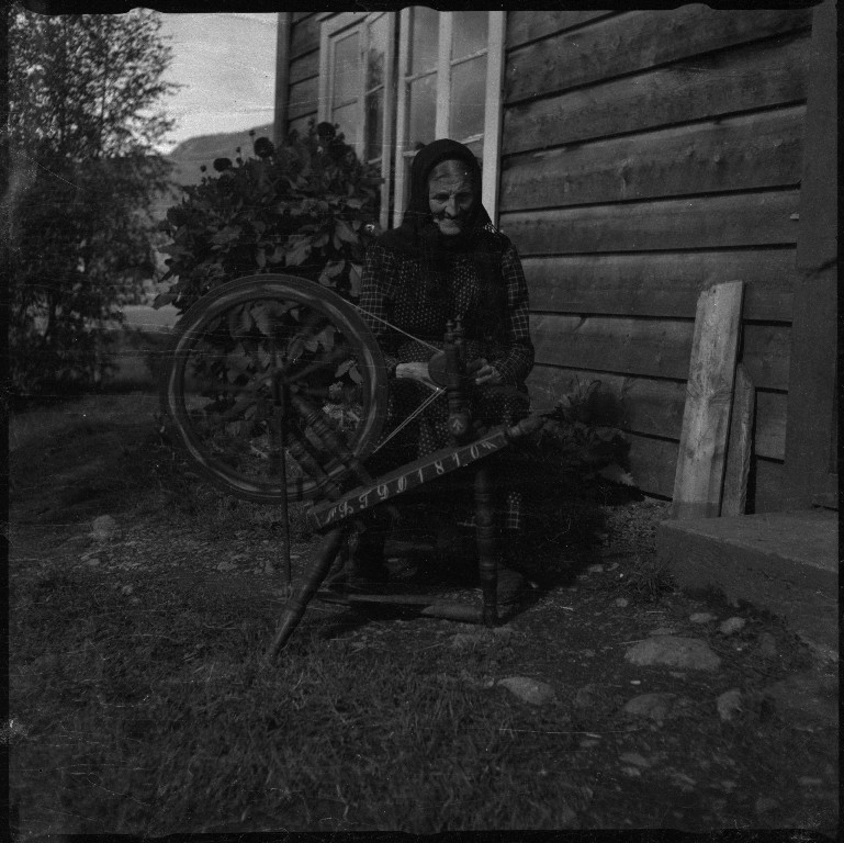 """Bilder fra Kvilldal i Suldal. Det er oversiktsbilder og bilder av enkeltgårder, bl.a. langs Kvilldalsåa. Det er også bilde av noen gutter ved Naustrabbane- På det ene naustet står det """"KVILDAL"""". Sissel Øyane spinner garn på rokken sin fra 1810, Sofie Øyane strikker og Paul L. Steinrbu sitter med hunden sin under et epletre. Det står høystakker til tørk flere steder."""