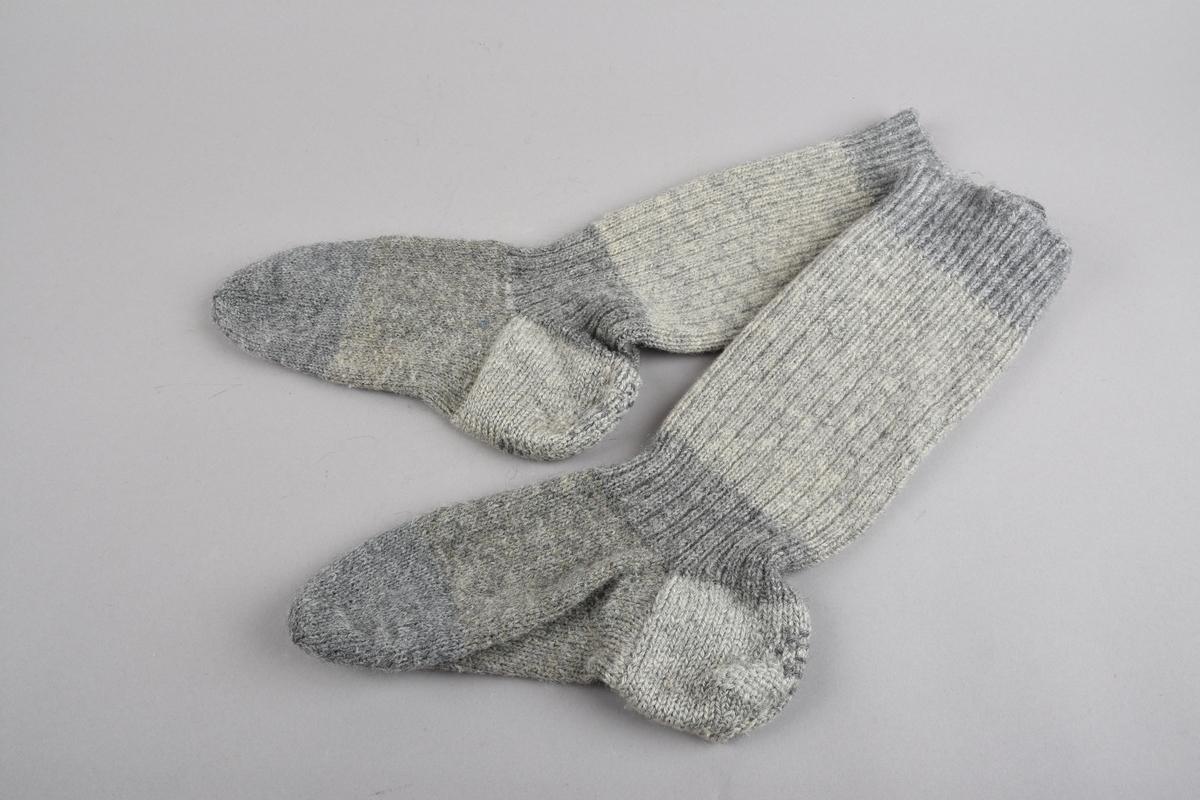 Eit par handstrikka ullstrømper/-sokkar til kvinne. Strømpene er strikka med breie felt i ulike gråfargar. Øvst to felt med vrangbord i 1 rett/1 vrang, der den øvste delen er strikka på i etterkant, ved at masker er plukka opp og strikka oppover med felling i kanten. Resten av leggen er strikka med 2 rette/2 vrange i to fargefelt. Hæl og fot er i glattstrikk med tre fargefelt. Hæl og framfot under, er stoppa med halvstopping som forsterking, hælen og stoppa med heilstopping.