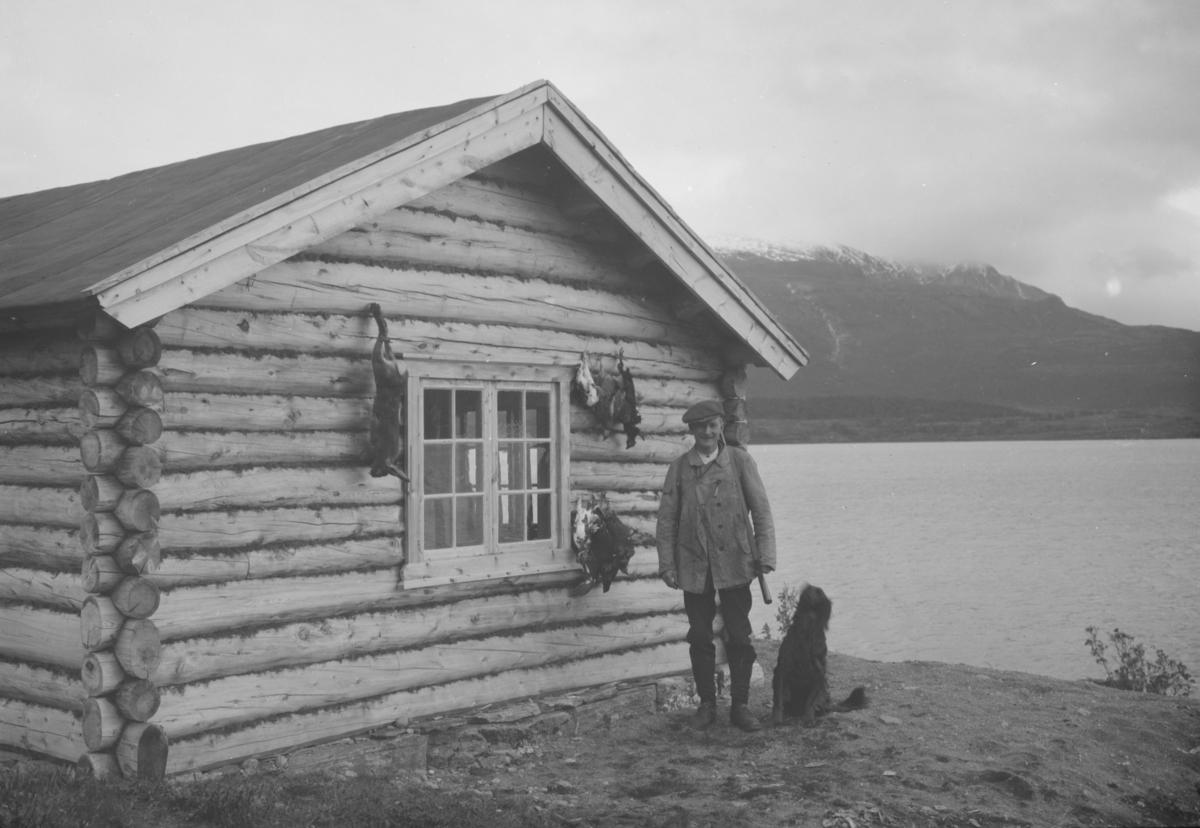 Jeger med hund og fangst ved hyttevegg og fjellvatn.