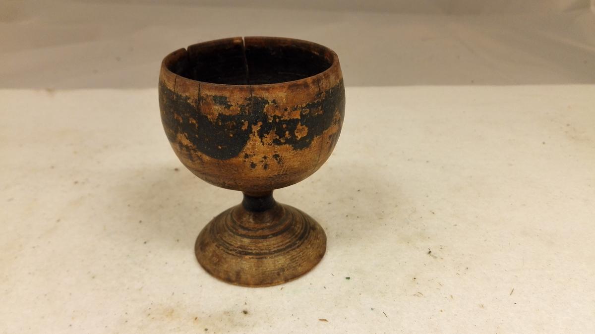 1 ølkappe.  Litet dreiet ølstøp av træ. Har utvendig malt sorte forsiringer.  Høide 8,3 cm, øvre diameter 6,4 cm.  Kjøpt av Ingeborg L. Eri, Lærdal.