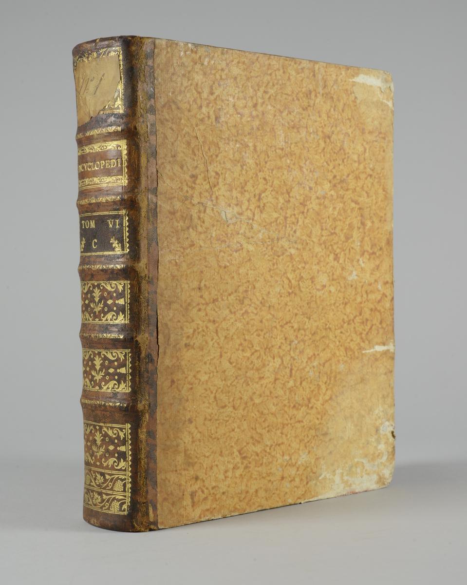 """Bok, """"Encyclopedie ou dictionnaire raisonné des sciences, des arts et des métiers"""" av Diderot och d`Alembert, utgiven 1778. Tredje upplagan, vol. 6 Halvfranskt band med pärmar av papp med påklistrat marmorerat papper, rygg av skinn med fem upphöjda bind med guldpräglad dekor, blindpressad och guldornerad rygg, titelfält med blindpressad titel och ett mörkare fält med volymens nummer. Påklistrad pappersetikett med nummerbeteckning med bläck. Med rött snitt."""