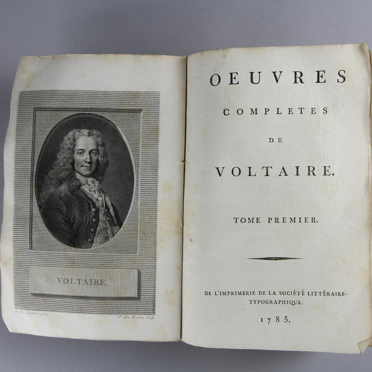 """Bok, häftad,""""Oeuvres complètes de Voltaire."""" del 6, tryckt 1785. Pärm av gråblått papper, skurna snitt. Blekt rygg med pappersetikett med tryckt text med volymens namn och nummer."""