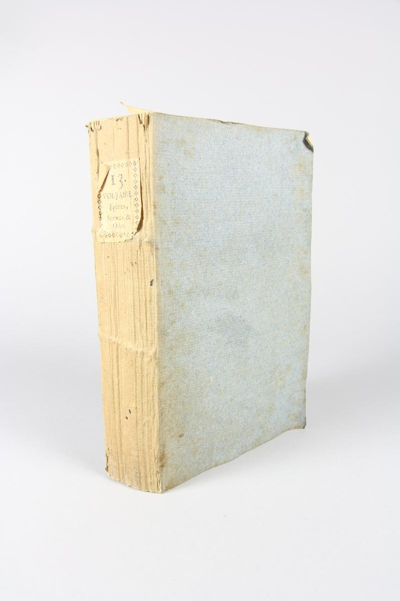 """Bok, häftad,""""Oeuvres complètes de Voltaire"""", del 13, tryckt 1785. Pärm av gråblått papper, på pärmens baksida klistrad sida ur annan bok. Med skurna snitt. På ryggen klistrad pappersetikett med tryckt text samt volymens nummer. Ryggen blekt."""