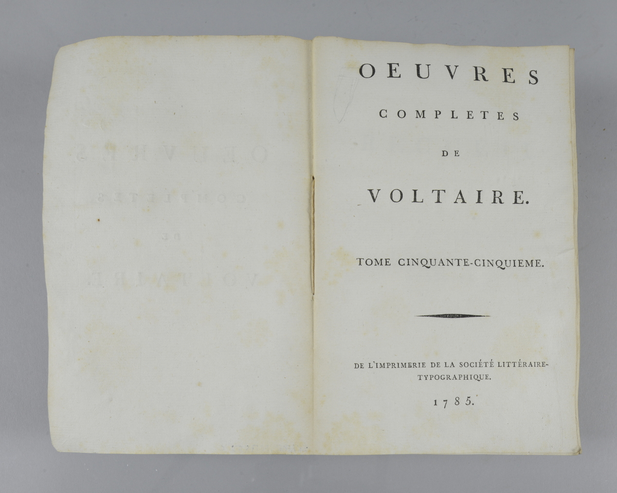 """Bok, häftad,""""Oeuvres completes de Voltaire. Receuil de lettres 1753-1757"""", del 55, tryckt 1785. Pärmen klädd med gråblått papper, på pärmens insidor klistrade sidor ur annan bok. Med skurna snitt. På ryggen pappersetikett med tryckt text samt volymens namn och nummer. Ryggen blekt."""