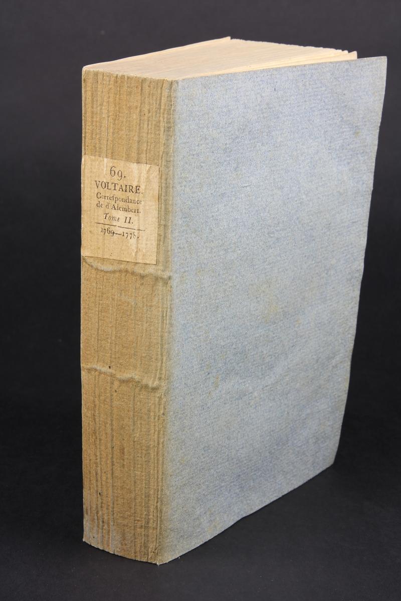 """Bok, häftad,""""Oeuvres complètes de Voltaire, Lettres de M. de Voltaire et de M. D´Alembert 1769-1778"""", del 69, tryckt 1785. Pärmen av gråblått papper, på pärmens insidor klistrade sior ur annan bok. Skurna snitt. På ryggen pappersetikett med tryckt text med volymens namn och nummer. Ryggen blekt."""