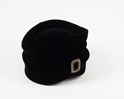 Damhatt av svart sammet. Fodrad med svart sidenfoder. Spänne i plast framtill på hatten. Märke innuti med text: Ruthel UPPSALA Tel. 31695 Drottninggat. 4.