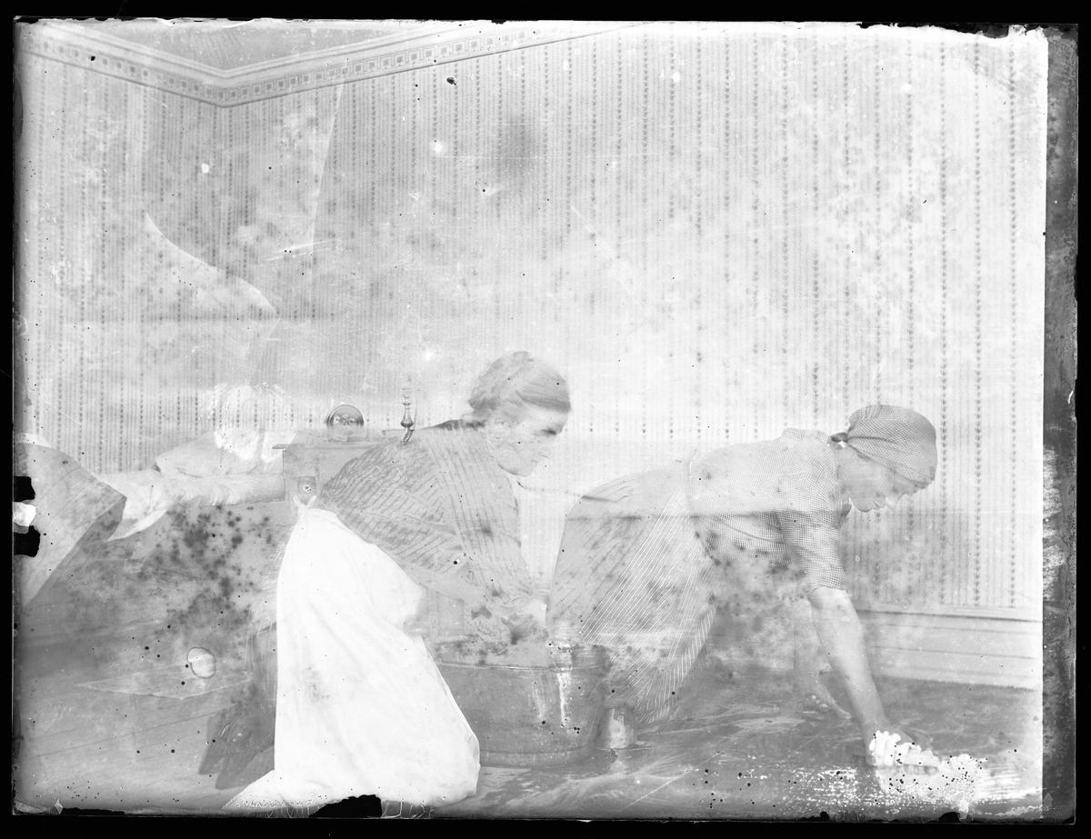 Hildur Norén och Ida Andersson ligger på knä och skurar ett trägolv. I bakgrunden står en enkelsäng och ett nattduksbord.