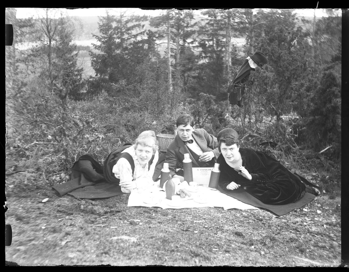Signe Thorsell, Hugo Larsson och Eva R ligger på filtar i gräset, röker och fikar. Framför dem är termosar, koppar och en flaska uppdukade. Fotot taget på Kristi himmelsfärdsdagen.
