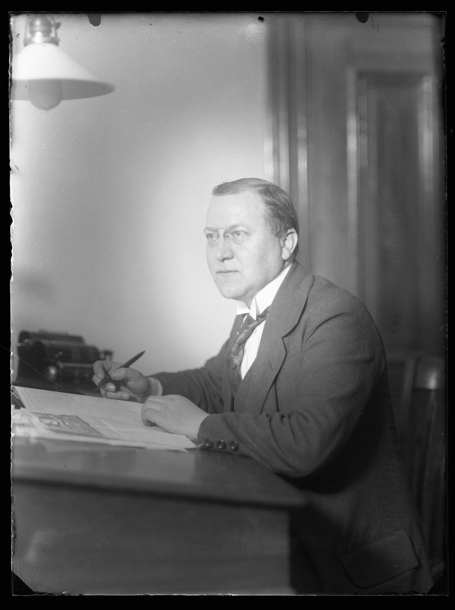 Porträtt av Harald Johansson sittandes vid ett skrivbord.
