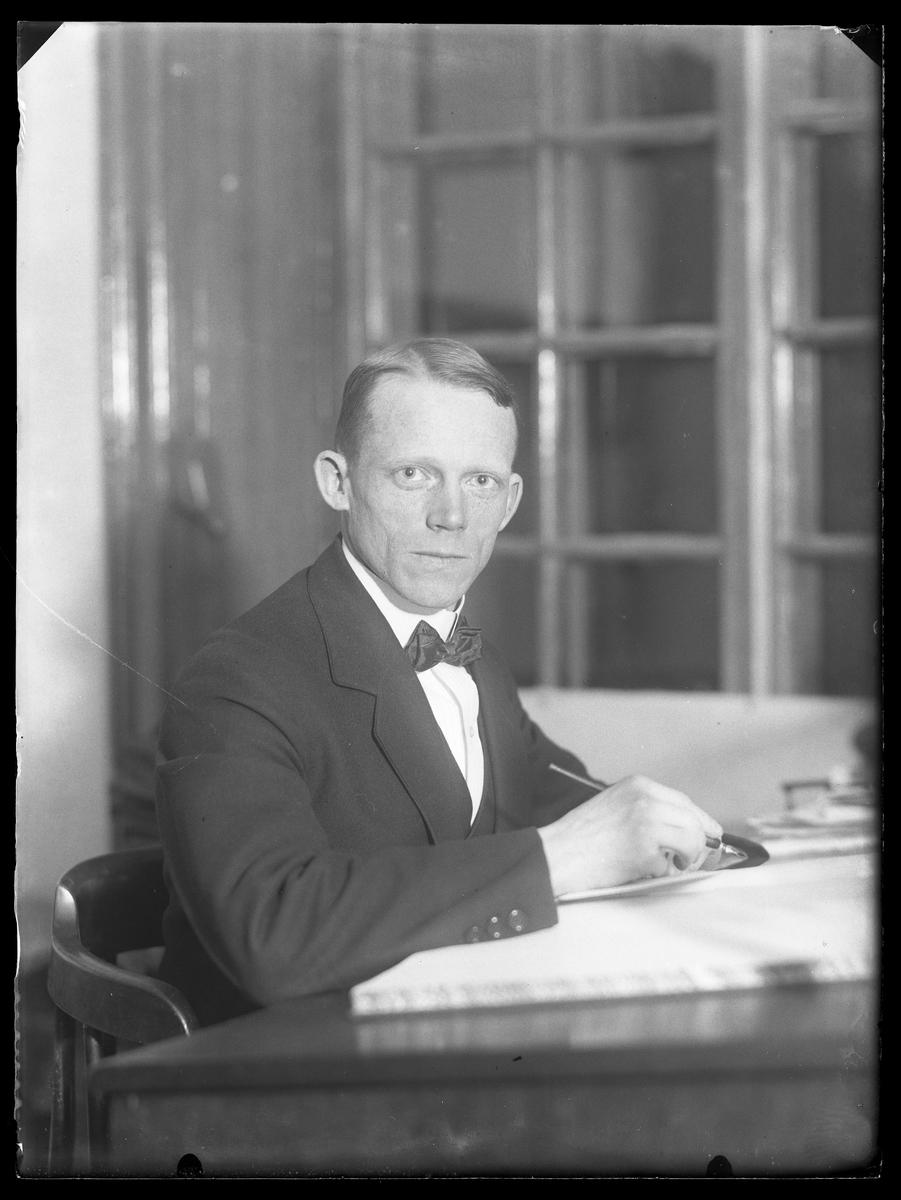 Ernst Claesson porträtterad arbetandes vid skrivbord.