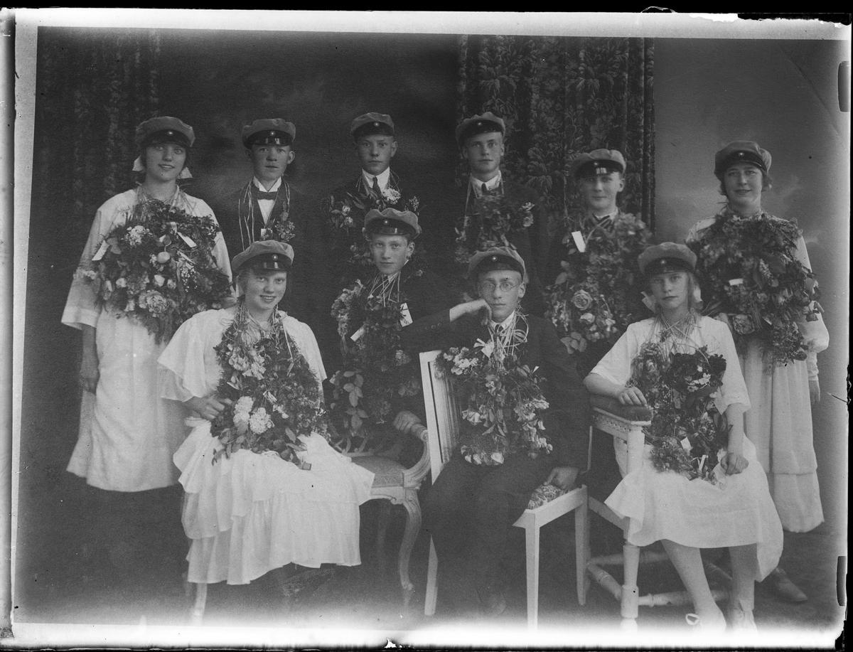 Gruppbild med fyra flickor och sex pojkar. Alla har blommor runt halsen och studentmössa.