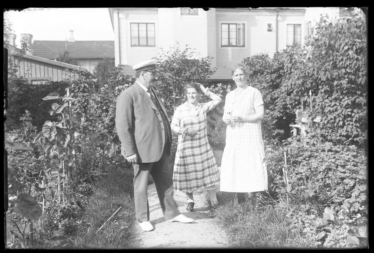 """En man i kostym, studentmössa och ljusa tygskor samt två kvinnor i rutiga sommarklänningar står på en grusgång i en lummig trädgård. I bakgrunden syns ett hus. I fotografens anteckningar står det """"Fam. Wincrantz"""". Bilden är tagen i samband med herr och fru Wincrantz 50årsdag."""