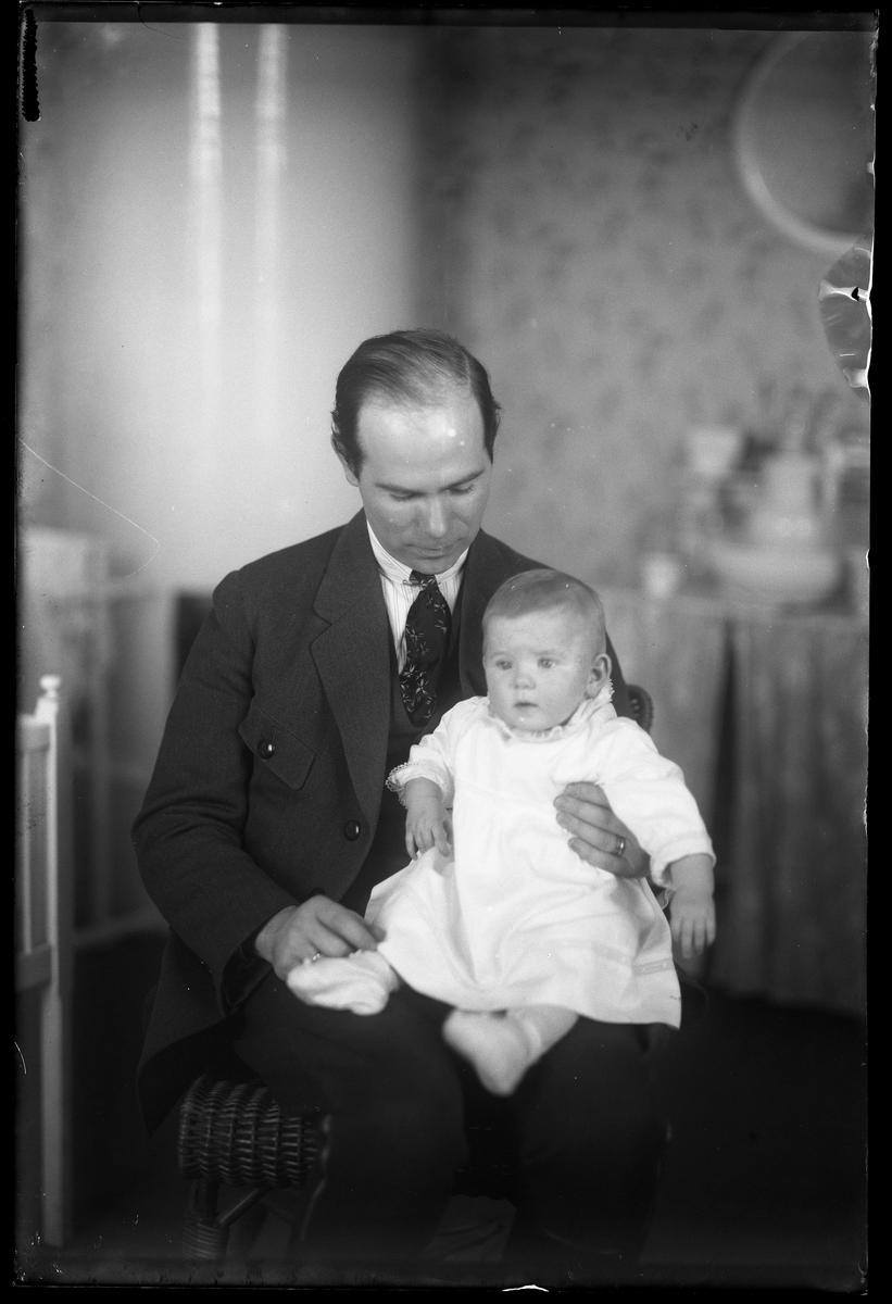 """En leende man sitter i en barnkammare med sin dotter i knät. I fotografens anteckningar står det """"Ing[enjör] Berg med dotter"""". Tolkat som Gunnar Teodor Berg med dottern Elsa Margareta."""
