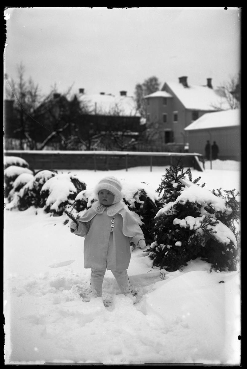 """En liten flicka, tolkad som Elsa Margareta Berg, i vita vinterkläder står i snön med en kvist i handen. I bakgrunen syns ett lägenhetshus. I fotografens anteckningar står det """"Ing[enjör] Bergs flicka""""."""