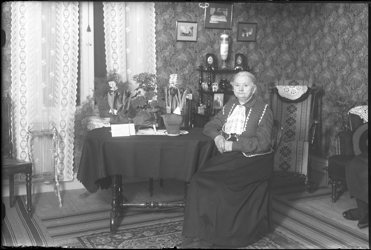 """En kvinna fotograferad vid ett bord med blommor. I fotografens anteckningar står det """"Fru Sunnergren"""", tolkat som Matilda Sunnergren Olsson som fyllde 65år i samband med att bilden togs."""