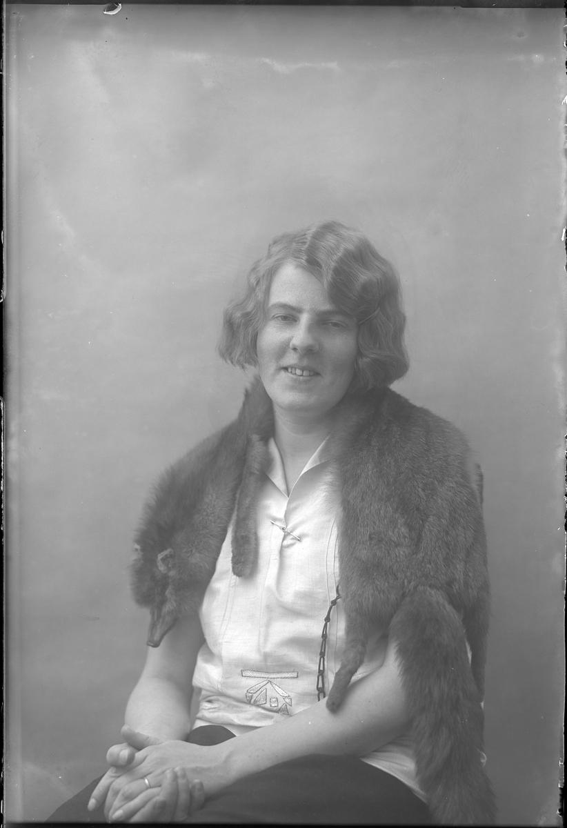 Porträtt av Lizzie Skoglund med vit blus och en räv om axlarna.