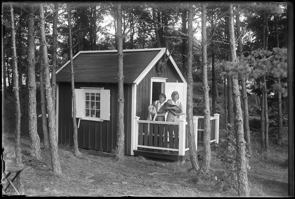 """Två kvinnor, med varsin hund i famnen, står på verandan till en liten stuga. I fotografens egna anteckningar står det """"Greta Nilssons ö (Stugan)""""."""
