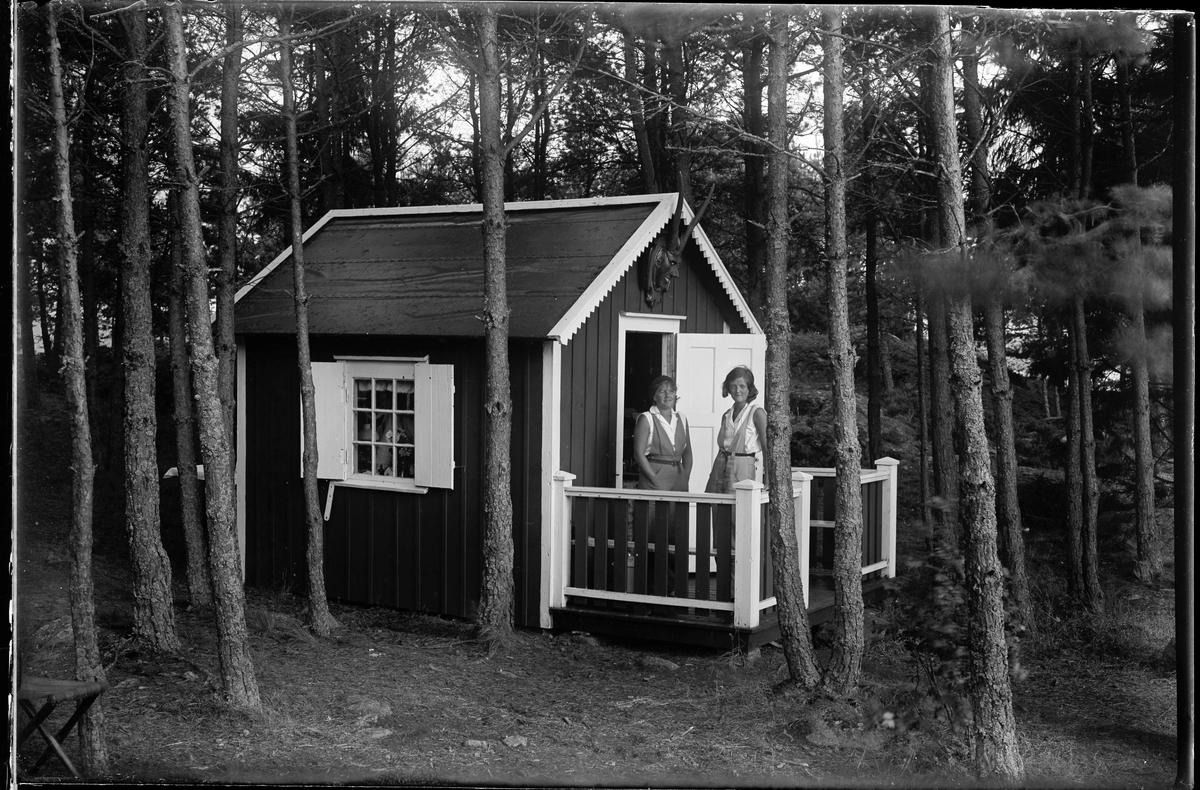 """Två kvinnor står på verandan till en liten stuga. I fotografens egna anteckningar står det """"Greta Nilssons ö (Stugan)""""."""