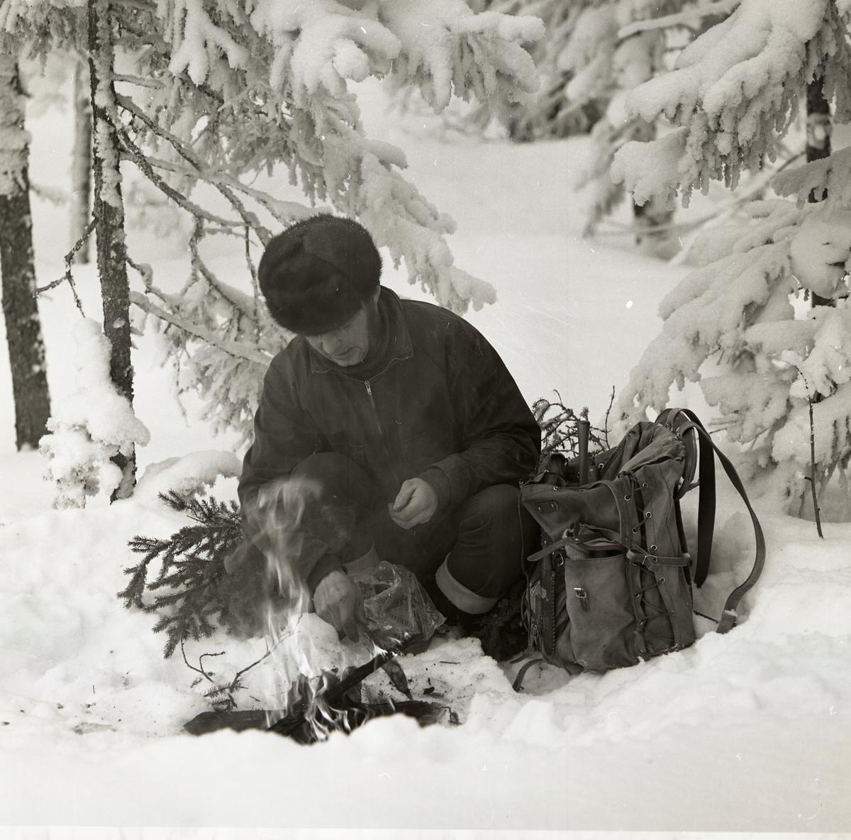 En man sitter på huk i snön och tänder en brasa den 24 februari 1970.