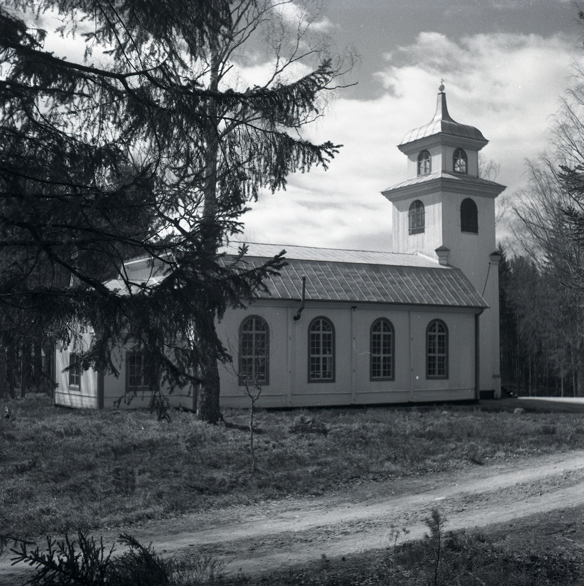 Annefors kyrka med mansardtak bakom en gran.