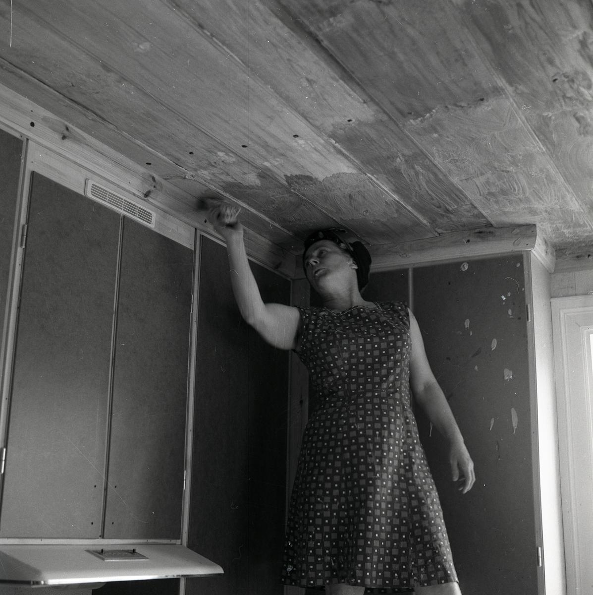 En kvinna skrubbar taket med en skurborste, juni 1968.