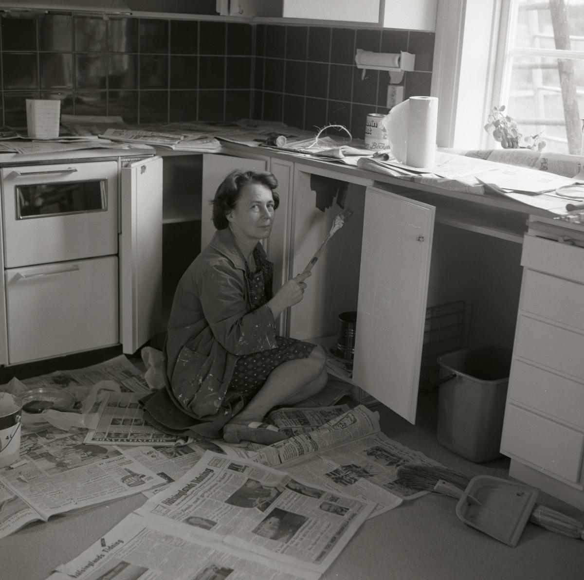 En kvinna sitter på golvet och målar köksluckor i bostadshuset vid gården Sunnanåker, 1967-68.