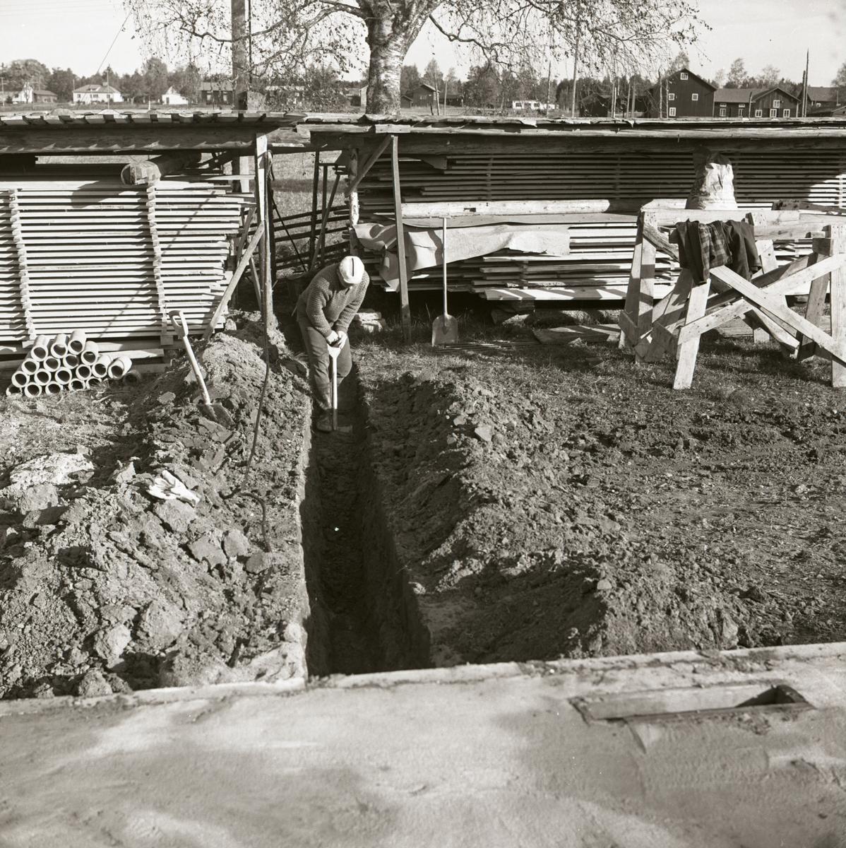 En man gräver ett dike för nedläggning av avloppsrör under byggnationen av ett bostadshus vid gården Sunnanåker, 1967.