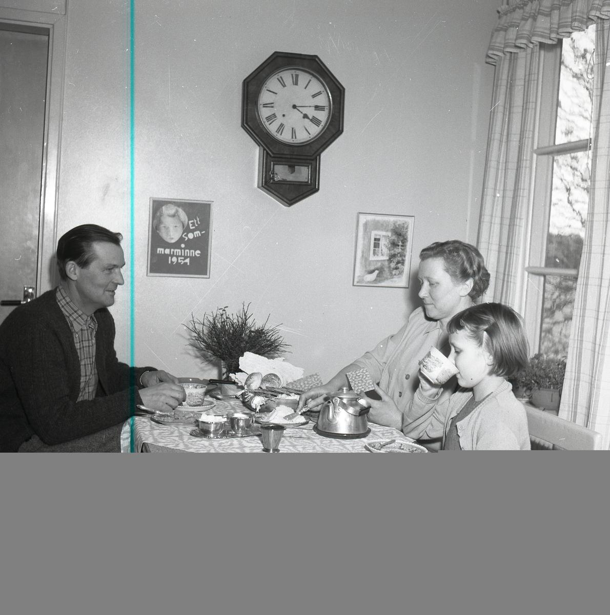 Två vuxna och ett barn sitter vid ett köksbordoch dricker te.