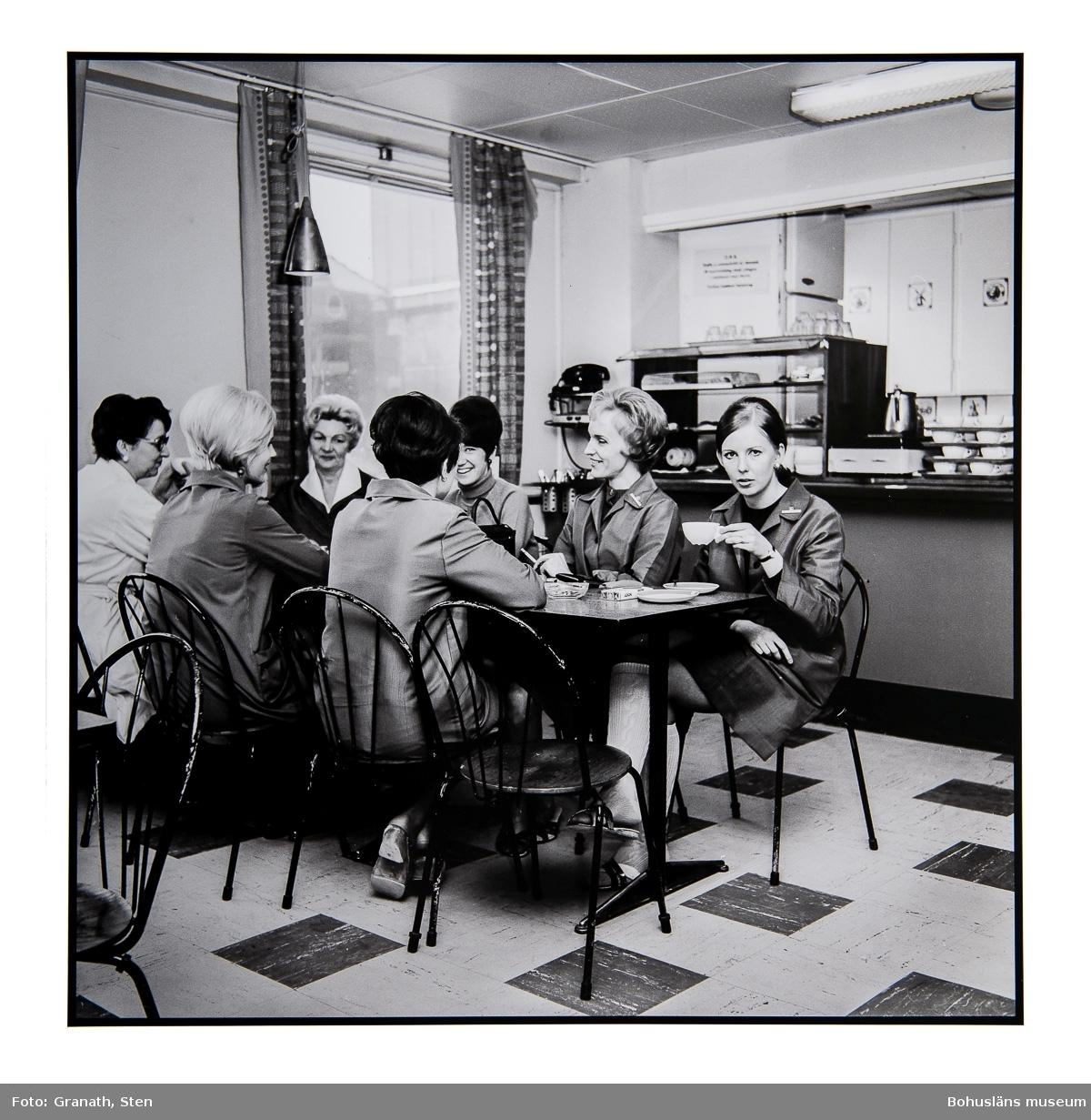 Fikapaus på EPA-varuhuset. Sju kvinnor sitter kring ett rektangulärt bord. Fyra av kvinnorna har likadana arbetsuniformer på sig. Bakom bordet finns en disk med porslin, en kylmonter och en kaffeperkulator.