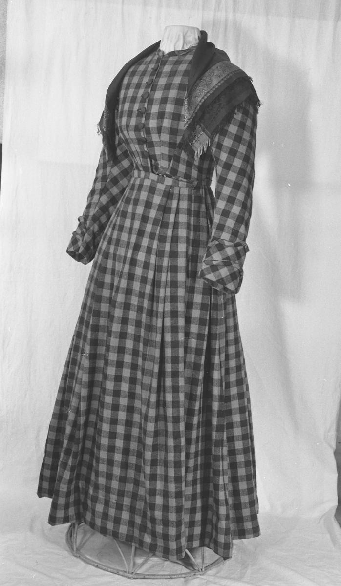 Delt i livet, knepping i kjolelivet, 7 knapper trekt med svart silke.  Anna Skavhaugen vet ikke no om denne kjolen. Hun har aldri sett tørklær brukt slik som det er satt på denne kjolen og på andre kjolene fra Skavhaugen som er på museet.