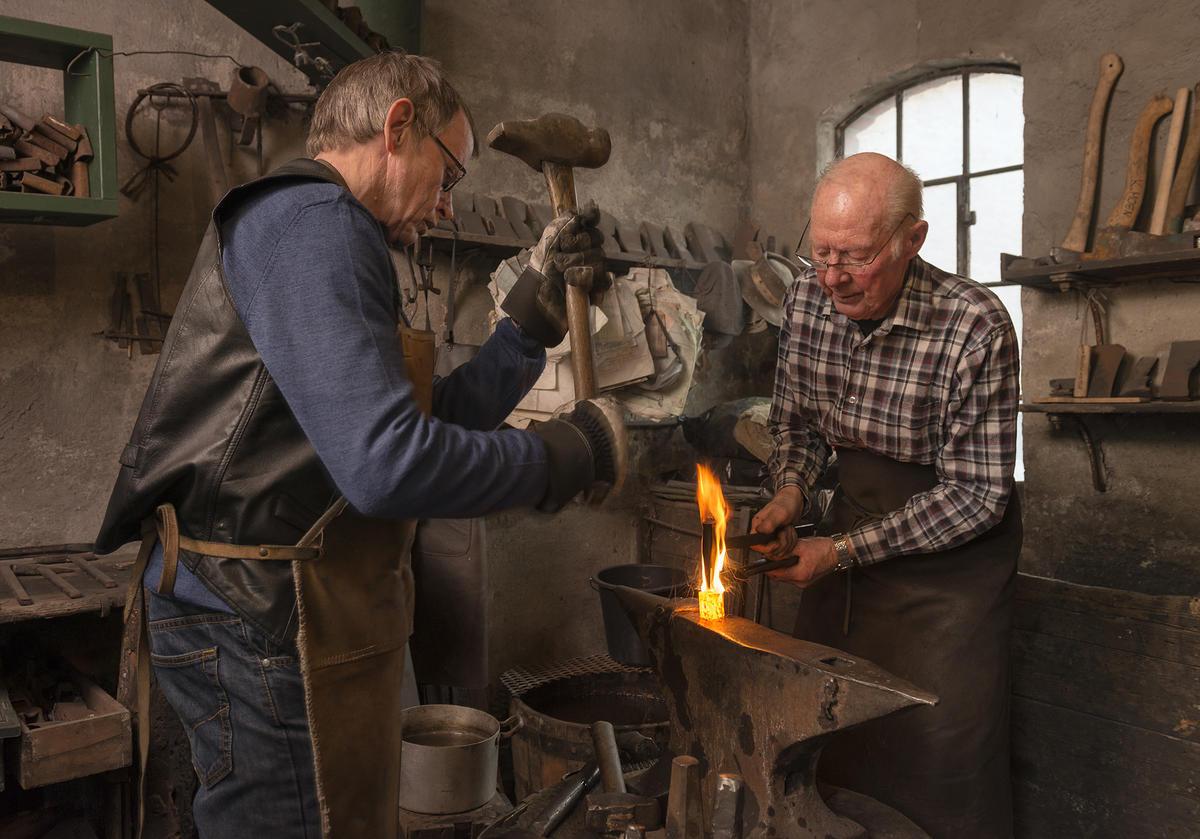 Smeden Oddbjørn Knudsen og oppslageren John Lystad lager merkeøks.