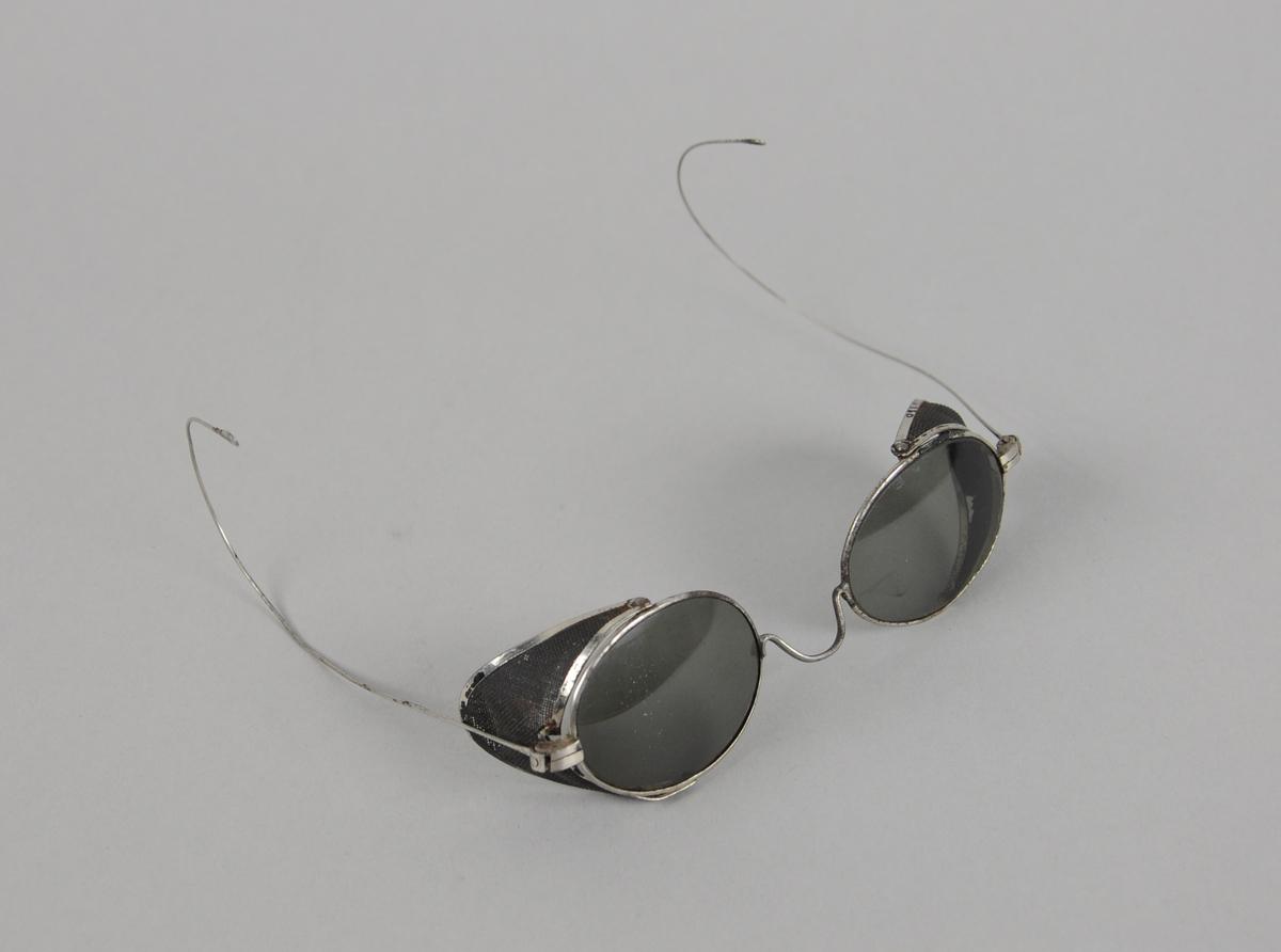 Ovale solbriller med metallinnfatning og beskyttelse på yttersidene av brilleglassene. Smale stenger med store bøyler ytterst.