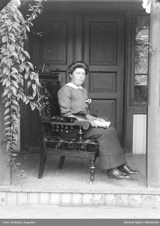 Portrett av ukjent kvinne, ved inngangsparti til våningshus.