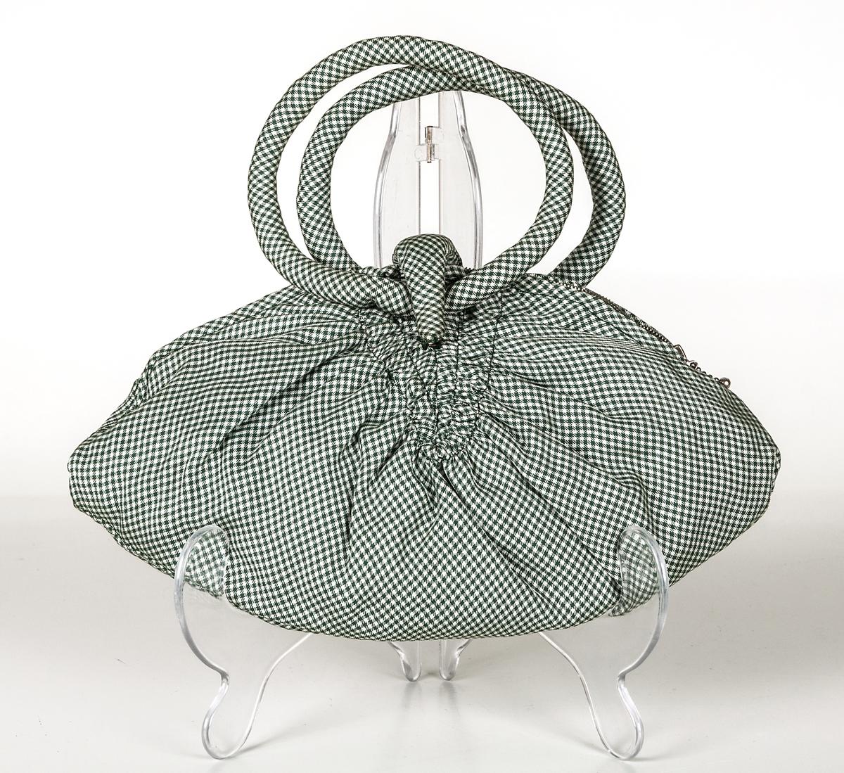 Handväska, kvinno. Smårutmönstrad taft, grönt och vitt. Rynkad rugbybollsliknande form. Vit metalldragedja. Två runda handtag. Inuti, grönt taftfoder.