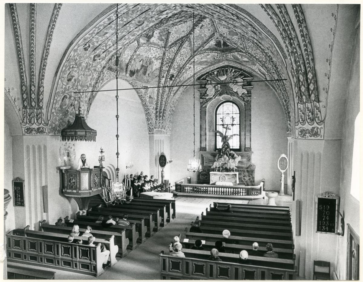 Dingtuna sn, kyrkan.  Gudstjänst i Dingtuna kyrka, med prästen i predikstolen. Bilden tagen mot altaret och med besökare sittande i kyrkbänkarna.