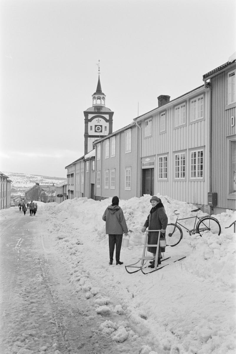En kvinne med spark i bygatene på Røros.