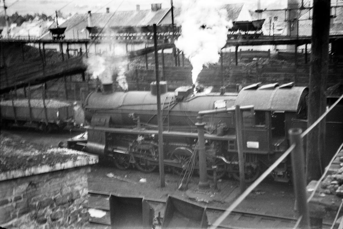 Damplokomotiv type 31b nr. 419 ved lokomotivstallen på Voss stasjon. I bakgrunnen vagger som ble benyttet til transport av kull til damplokomotivene.