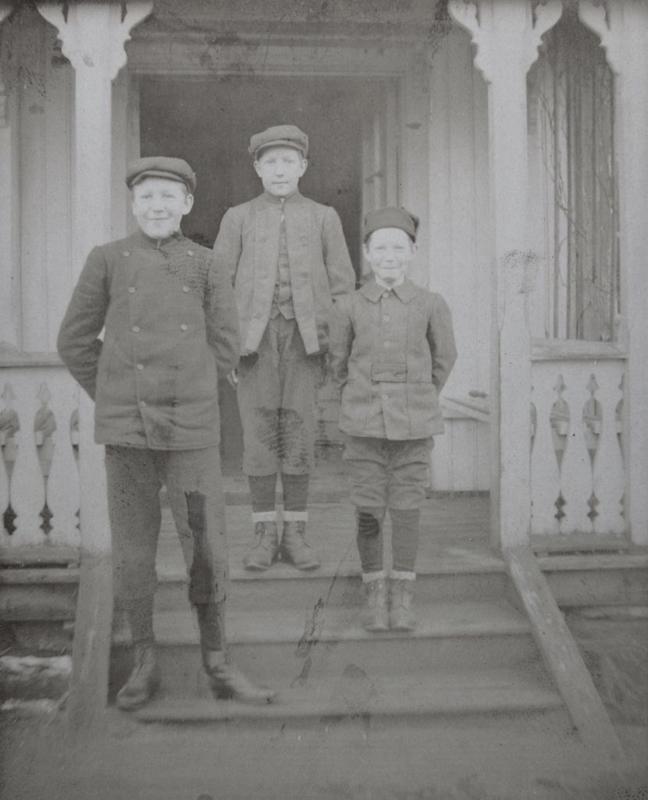 Brødrene Ragnvald, Anders og Asbjørn Wang på trappen utenfor den første bestyrerboligen på Ørje Brug.